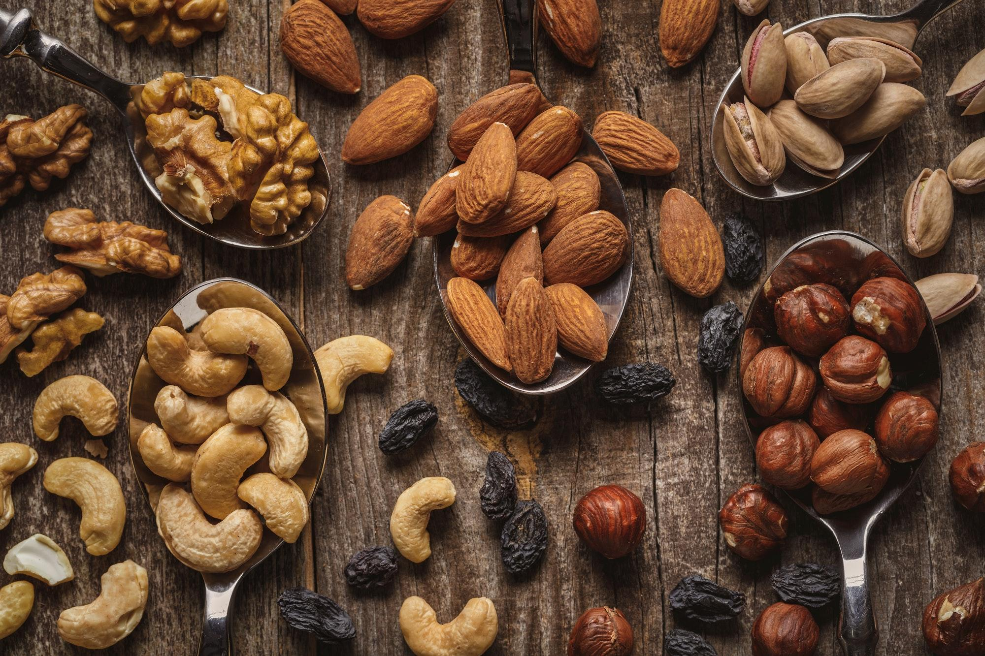 flat lay with nuts in spoons on wooden tabletop